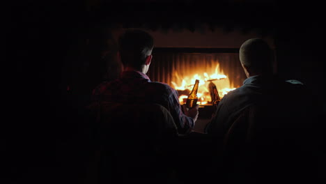 Silhouettes-Of-Two-Men-By-The-Fireplace-Relaxing-With-Bottles-Of-Beer-In-Their-Hands