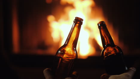 Two-Bottles-Of-Beer-In-The-Hands-Of-Men-On-A-Background-Of-Fire-In-A-Fireplace-Close-Up-Shot