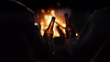 Friends-Drink-Beer-Sitting-By-The-Fireplace-Rear-View