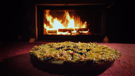 Appetizing-Pizza-On-A-Red-Tablecloth-On-The-Background-Of-The-Fireplace-Where-The-Fire-Is-Burning-St