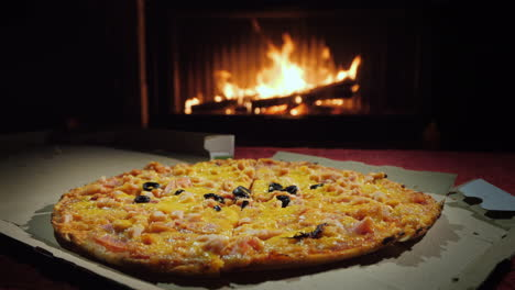Pizza-In-A-Cardboard-Box-On-The-Table-Against-The-Background-Of-The-Fireplace-Static-Shot