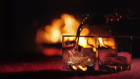Whiskey-Is-Poured-Into-A-Glass-With-Ice-On-The-Background-Of-The-Fireplace