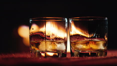 Two-Glasses-Of-Whiskey-Stand-On-The-Table-In-The-Background-A-Fire-Burns-In-The-Fireplace