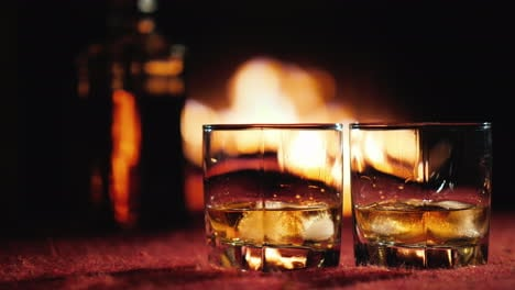 Two-Glasses-Of-Whiskey-With-Ice-In-The-Background-A-Bottle-And-A-Fireplace-Where-The-Fire-Is-Burning
