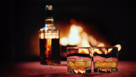 Strong-Alcohol-In-Two-Glasses-And-A-Bottle-In-The-Background-A-Fire-Burns-In-The-Fireplace