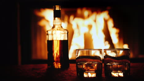 Two-Glasses-And-A-Bottle-Of-Whiskey-Stand-On-The-Table-Against-The-Background-Of-A-Hot-Fireplace