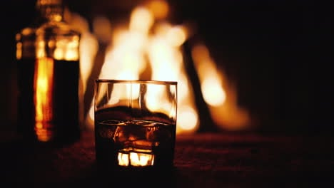 A-Glass-Of-Whiskey-And-A-Bottle-On-The-Table-In-The-Background-A-Fire-Burns-In-The-Fireplace