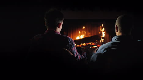 Two-Handsome-Men-Rest-By-The-Fireplace-Slowly-Drinking-Brandy