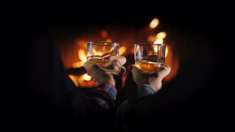Hands-Of-Two-Men-With-Glasses-Of-Whiskey-On-The-Background-Of-The-Fireplace-Male-Rest