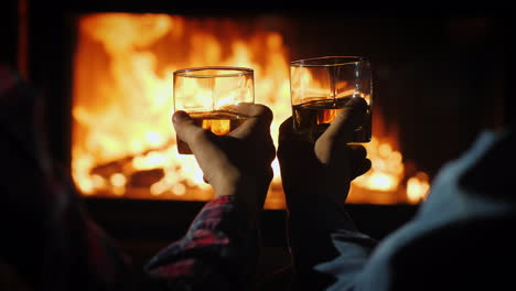 Two-Men-Are-Drinking-Strong-Alcohol-By-The-Fireplace-In-The-Frame-Are-Visible-Hands-With-Glasses-Aga