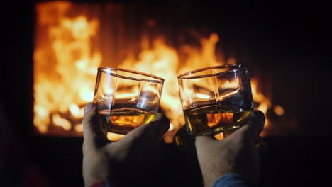 Two-Male-Hands-With-Glasses-Of-Whiskey-With-Ice-On-The-Background-Of-The-Fireplace-Winter-Escape-Con