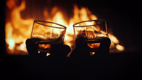 Two-Glasses-Of-Whiskey-With-Ice-In-Male-Hands-The-Fire-From-The-Fireplace-Is-Reflected-In-The-Drink-