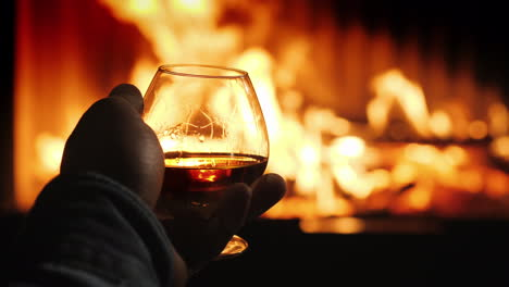 A-Man-Holds-A-Glass-With-Alcohol-In-His-Hand-The-Fire-From-The-Fireplace-Is-Reflected-In-The-Drink-W