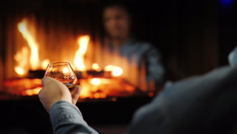 A-Man-Drinks-Brandy-By-The-Fireplace-His-Face-Is-Reflected-In-The-Glass-Of-The-Furnace