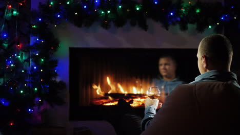 A-Man-With-A-Glass-Of-Spirits-Sits-By-The-Fireplace-Decorated-For-Christmas