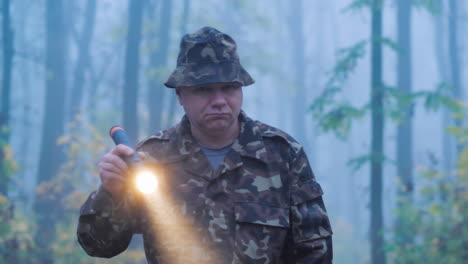 A-Man-In-Camouflage-Is-Walking-Through-The-Forest-With-A-Flashlight-In-His-Hand-Wet-Rainy-Weather-In