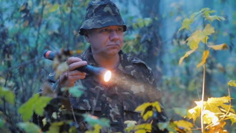 A-Man-Shines-A-Flashlight-At-Dusk-In-The-Forest-Search-Operation