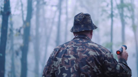 A-Man-In-Camouflage-Is-Walking-Through-The-Forest-Lighting-His-Way-In-The-Fog-Search-For-The-Missing