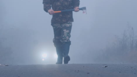 Aggressive-Man-With-An-Ax-Is-Walking-In-The-Fog-Towards-The-Car