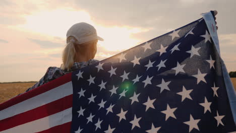 A-Woman-Farmer-With-The-Usa-Flag-Stands-In-A-Field-Of-Ripe-Wheat-At-Sunset-Independence-Day-Concept