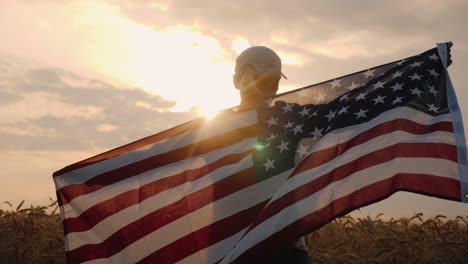 Middle-Aged-Woman-With-Usa-Flag-Stands-In-A-Wheat-Field-At-Sunset-Independence-Day-Concept