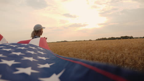 A-Patriotic-Farmer-With-A-Us-Flag-Stands-Near-A-Field-Of-Ripe-Wheat-Holds-A-Flag-For-One-Of-The-Edge