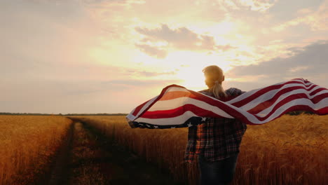A-Woman-With-A-Usa-Flag-Runs-Across-A-Wheat-Field-In-The-Sun-s-Rays-At-Sunset