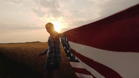 First-Person-View-Of-A-Woman-Carrying-The-Usa-Flag-At-One-Of-The-Edges-Go-Near-The-Wheat-Field-At-Su