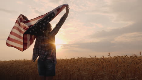 Woman-With-Usa-Flag-Runs-In-The-Sun-On-A-Wheat-Field