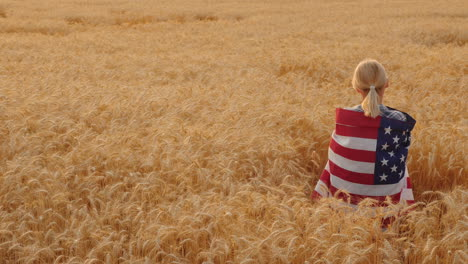 Woman-With-Usa-Flag-On-Her-Shoulders-Stands-In-A-Wheat-Field-Top-View