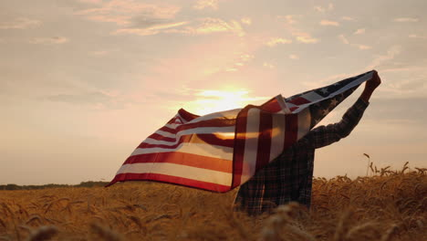 Man-Holds-Usa-Flag-Behind-Stands-In-A-Picturesque-Field-Of-Wheat
