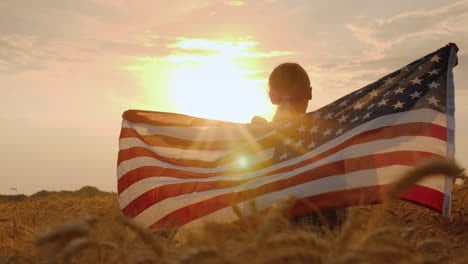 Woman-With-Usa-Flag-In-The-Rays-Of-The-Setting-Sun-Stands-In-A-Wheat-Field