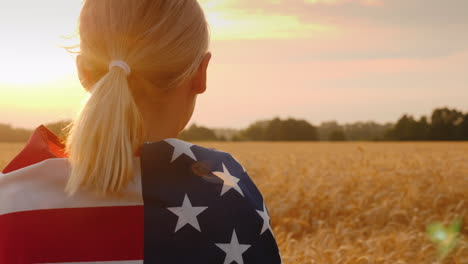 A-Woman-With-A-Usa-Flag-On-Her-Shoulders-Enjoys-A-Field-Of-Wheat-At-Sunset