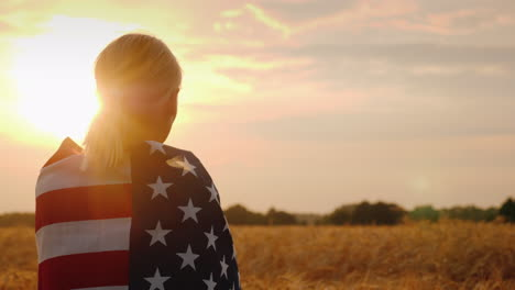 Silhouette-Of-A-Farmer-Woman-In-A-Wheat-Field-Usa-Flag-On-Her-Shoulders