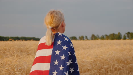 A-Young-Woman-With-The-Us-Flag-On-Her-Shoulders-Stands-In-A-Field-Of-Ripe-Wheat-4k-Video