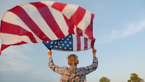 Woman-Running-With-American-Flag-In-Her-Hands-Flag-Waving-Against-Sky-Background-Rear-View