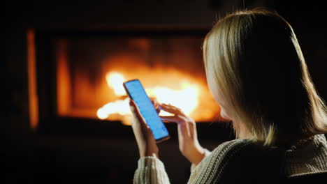 A-Woman-Uses-A-Smartphone-In-The-Evening-Sitting-By-The-Fireplace