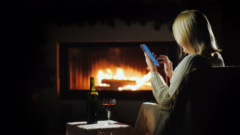 Nice-Evening-By-The-Fireplace-A-Woman-Uses-A-Smartphone-Near-A-Glass-Of-Wine