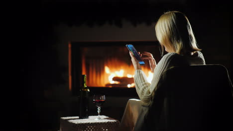 Woman-Shopping-Online-In-A-Pleasant-Atmosphere-By-The-Fireplace