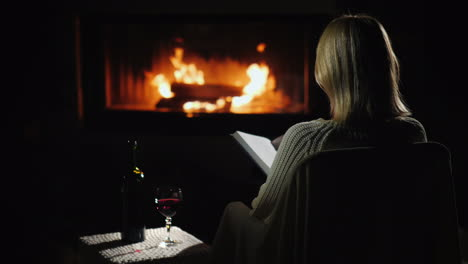 An-Evening-With-A-Book-And-A-Glass-Of-Wine-By-The-Fireplace-Woman-Reads-In-The-Living-Room