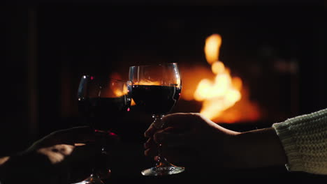 Clink-Glasses-With-Wine-Against-The-Background-Of-The-Fireplace-Where-The-Fire-Is-Burning