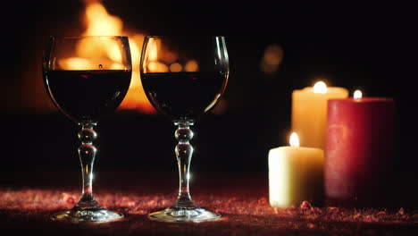 Two-Glasses-With-Red-Wine-Against-The-Background-Of-The-Fireplace-Where-The-Fire-Is-Burning
