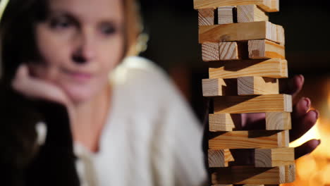 Portrait-Of-A-Woman-Playing-A-Board-Game-Where-You-Need-To-Pull-Out-Wooden-Blocks-From-The-Tower