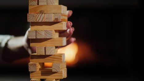 A-Hand-Pulls-Out-A-Wooden-Block-From-The-Tower-Board-Games-And-Evening-Together-Concept