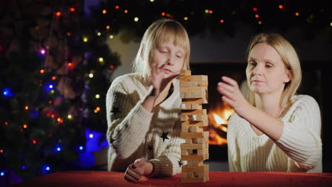 Mom-And-Daughter-Play-A-Board-Game-With-Wooden-Blocks
