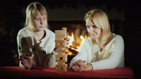 Mom-And-Daughter-Play-A-Board-Game-Together-Where-You-Need-To-Pull-Blocks-Out-Of-The-Tower