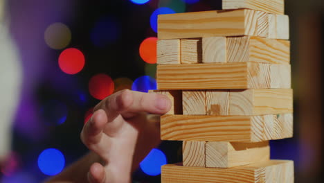 Pulling-A-Wooden-Block-Out-Of-The-Tower-Is-A-Game-For-Training-Accuracy-Close-Up-Shot