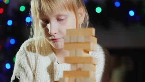 Girl-Pulls-Wooden-Blocks-From-The-Tower---A-Game-For-Training-Accuracy
