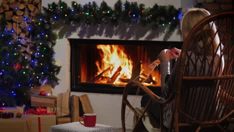 Evening-By-The-Fireplace-On-Christmas-Eve-An-Elderly-Woman-Knits-Warm-Clothes-4k-Video