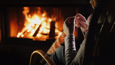 Female-Hands-With-Knitting-Needles---Knits-Warm-Clothes-Sitting-By-The-Fireplace